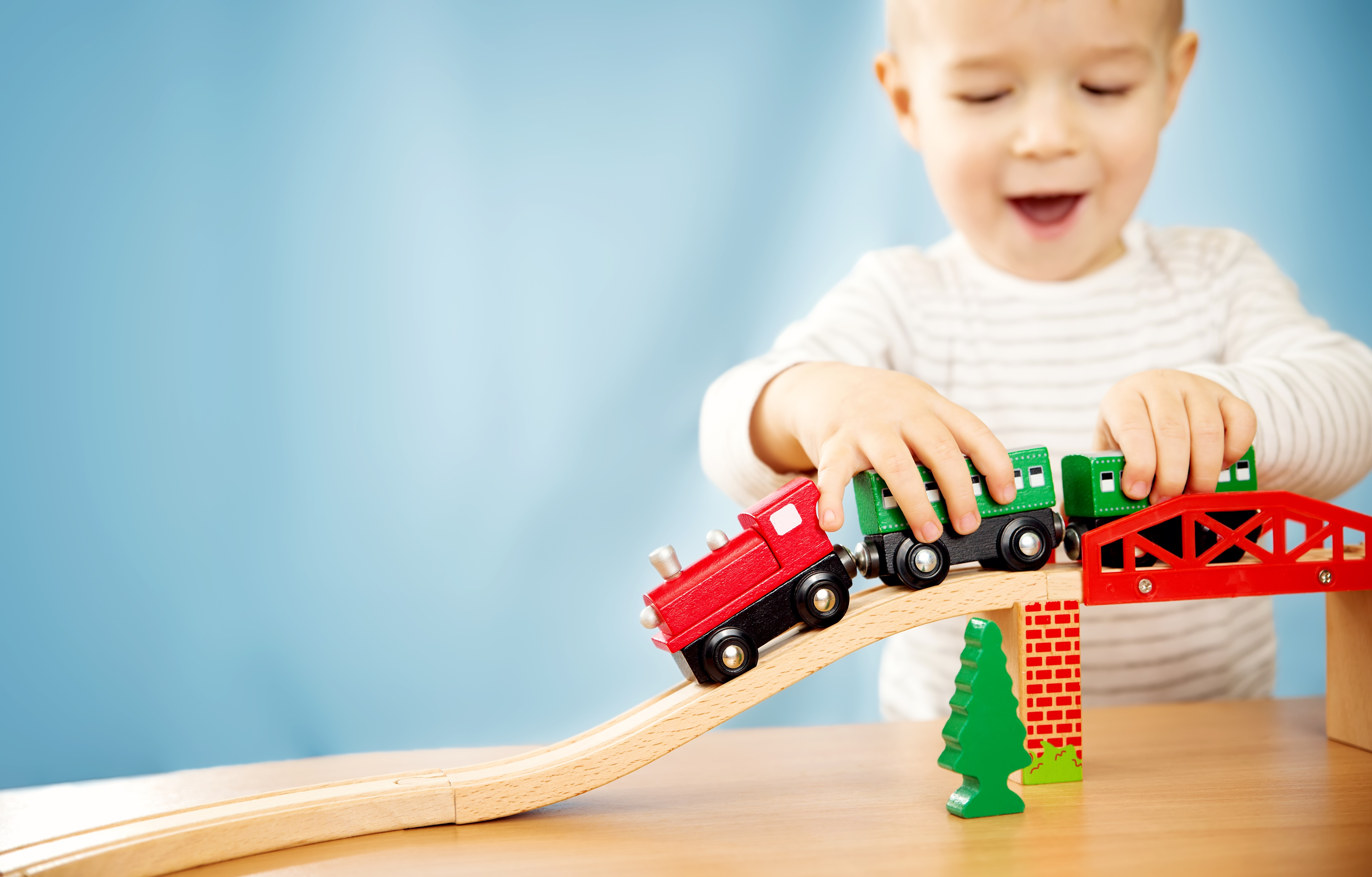 little boy playing with trains